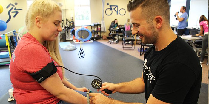 Hampton PT Guiding a patient through Blood Flow Restriction Therapy to help build strength