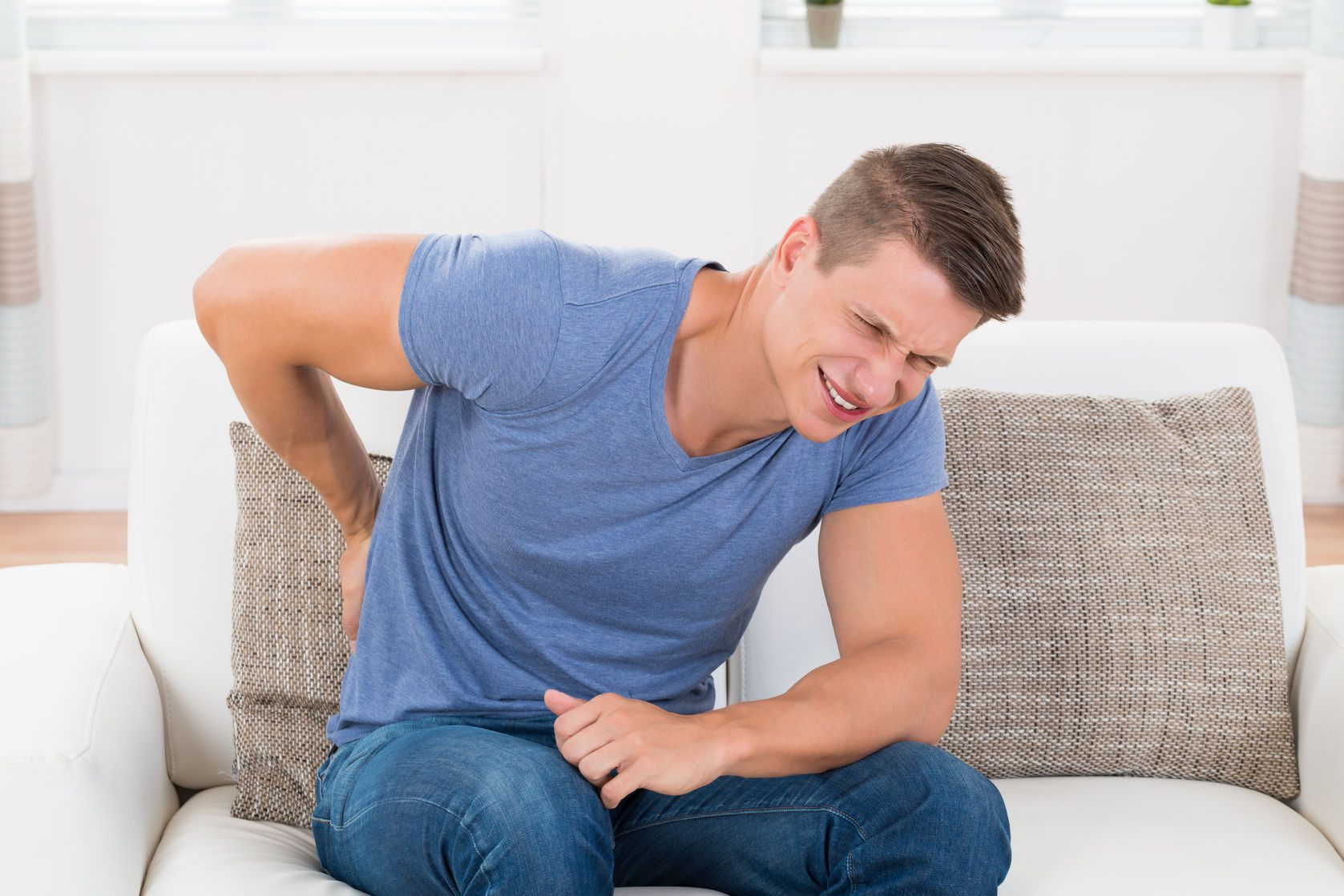 young man on sofa suffering from backpain at home