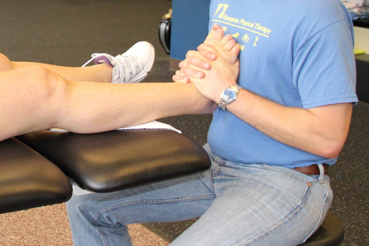 man massaging patient's foot