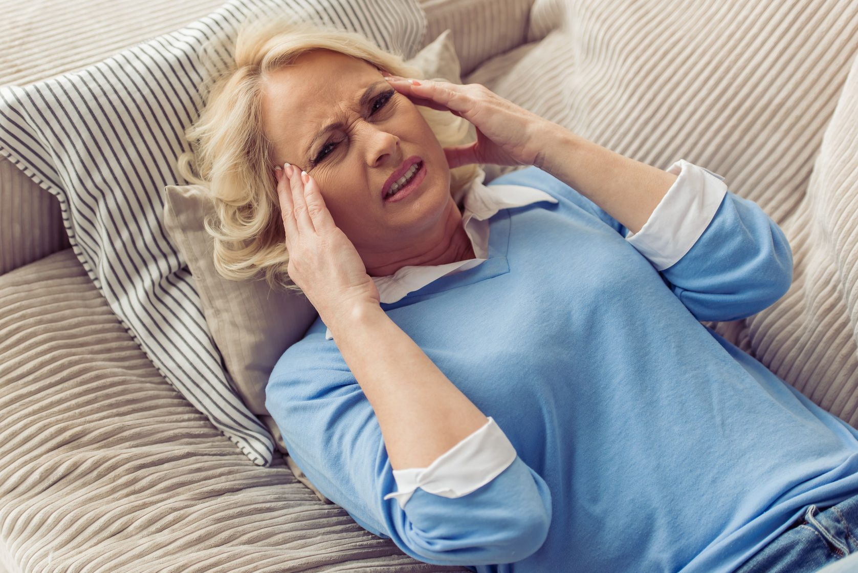 beautiful tired old woman in casual clothes is having a headache while lying on couch at home